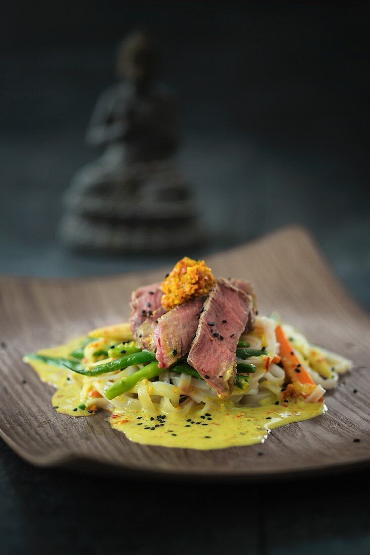Beef fillets with wide rice noodles and curry sauce (Asia)