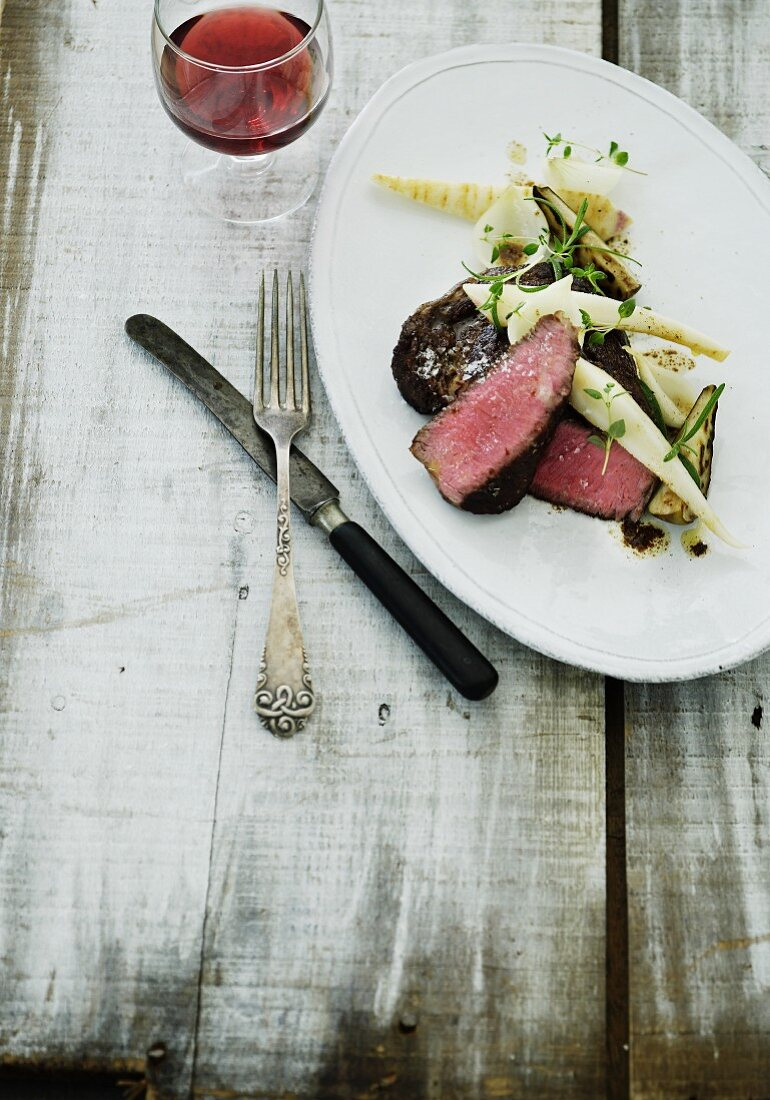 Rare venison steak with oven-roasted vegetables