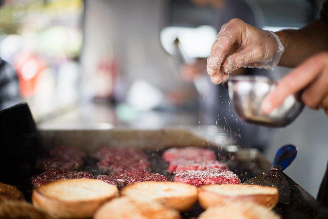 Meat patties being seasoned with salt