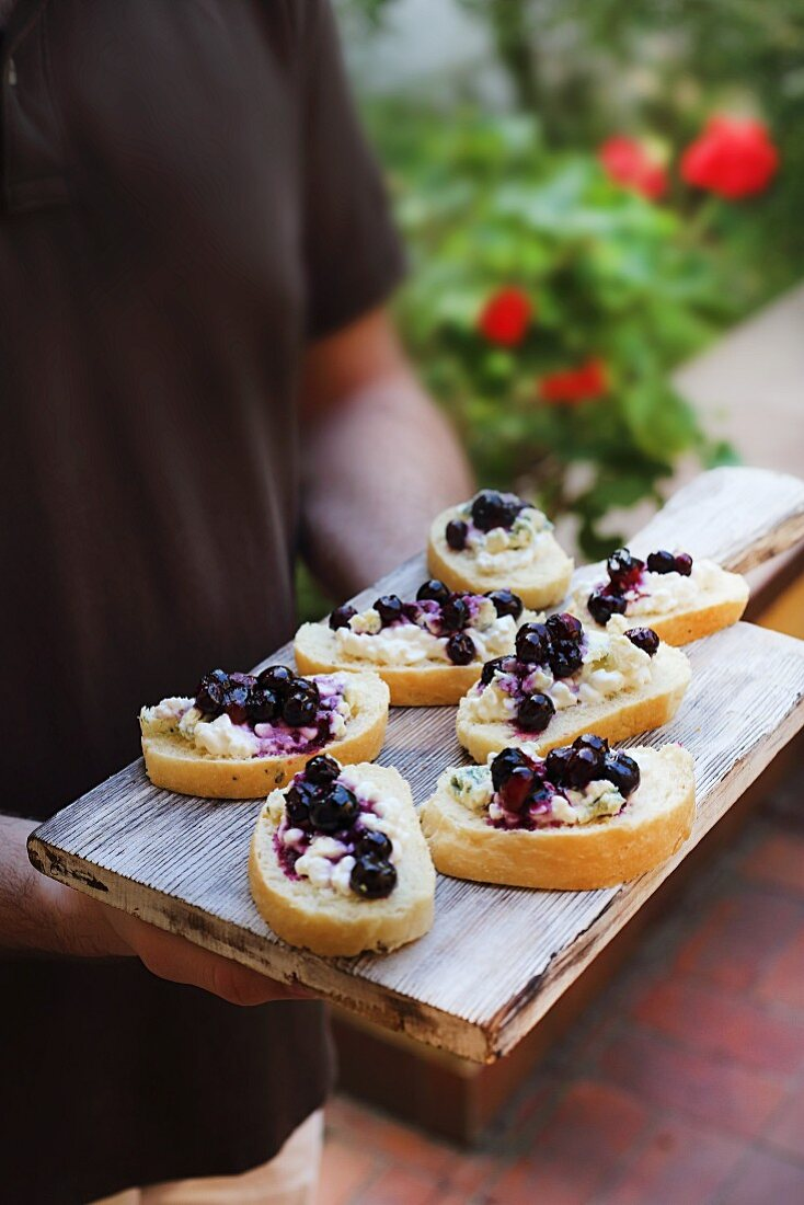 A person serving baguette canapés with gorgonzola cream and blueberries