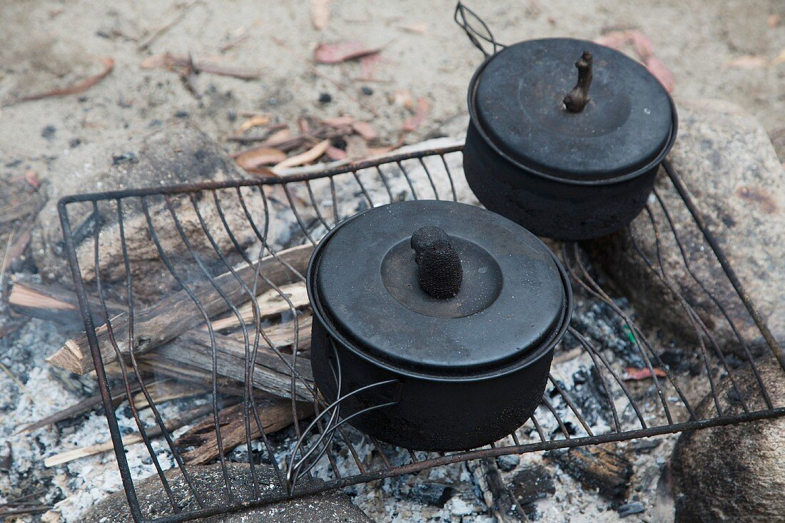 Cooking pot on an old wire rack over a campfire