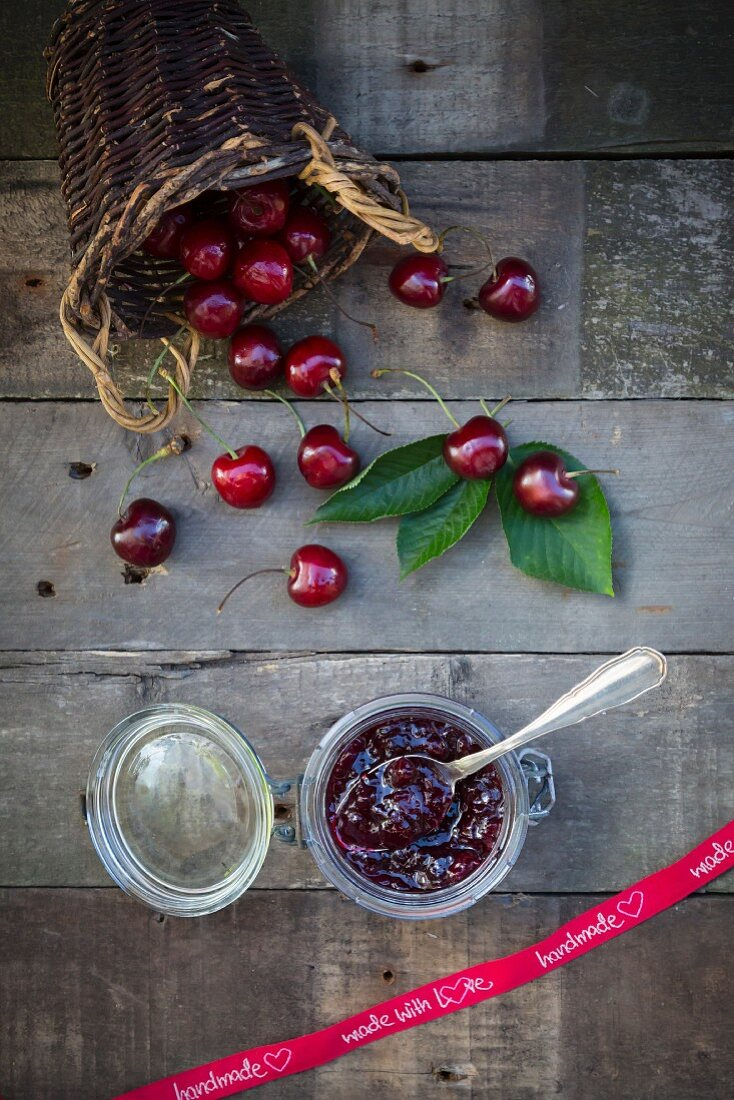 Homemade cherry jam in a jar next to a ribbon