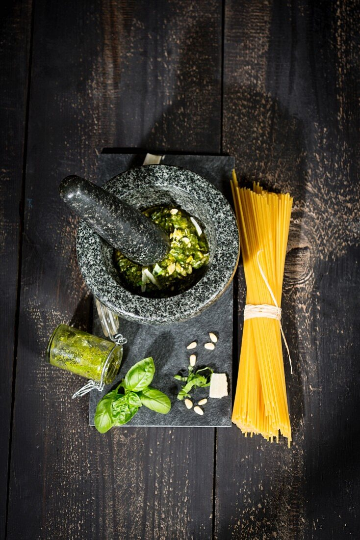 An arrangement of spaghetti, pesto alla genovese in a mortar with pesto ingredients
