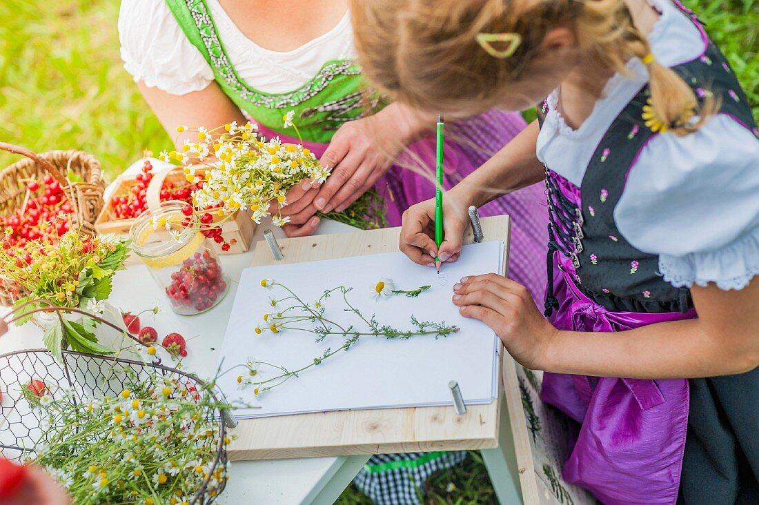 A little girl wearing a dirndl drawing flowers outside