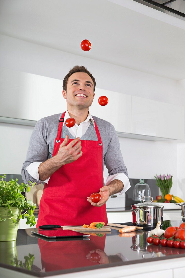 A man wearing an apron laughing and jugging tomatoes in a kitchen