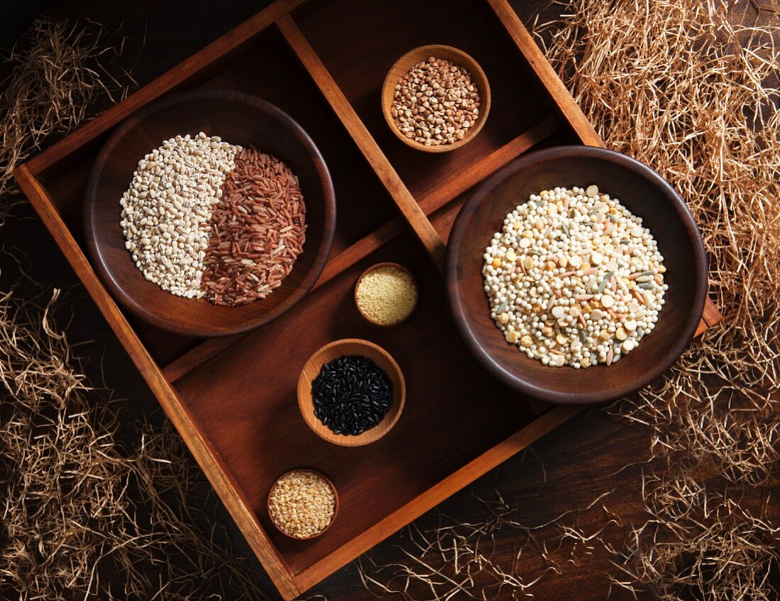 Various types of grains in wooden bowls in a rustic atmosphere