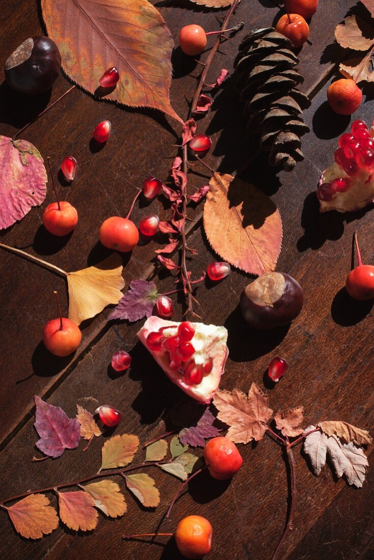 An autumnal arrangement with leaves, chestnuts and pomegranate seeds