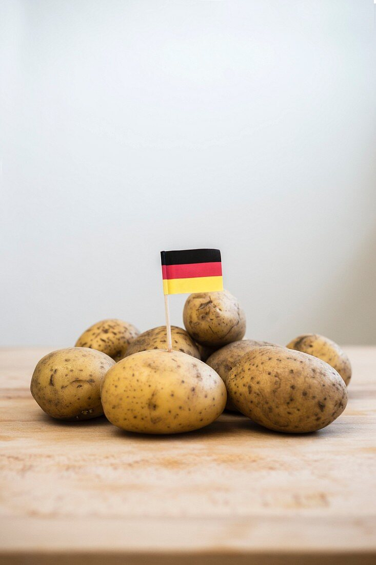 A paper German flag in the middle of a pile of potatoes