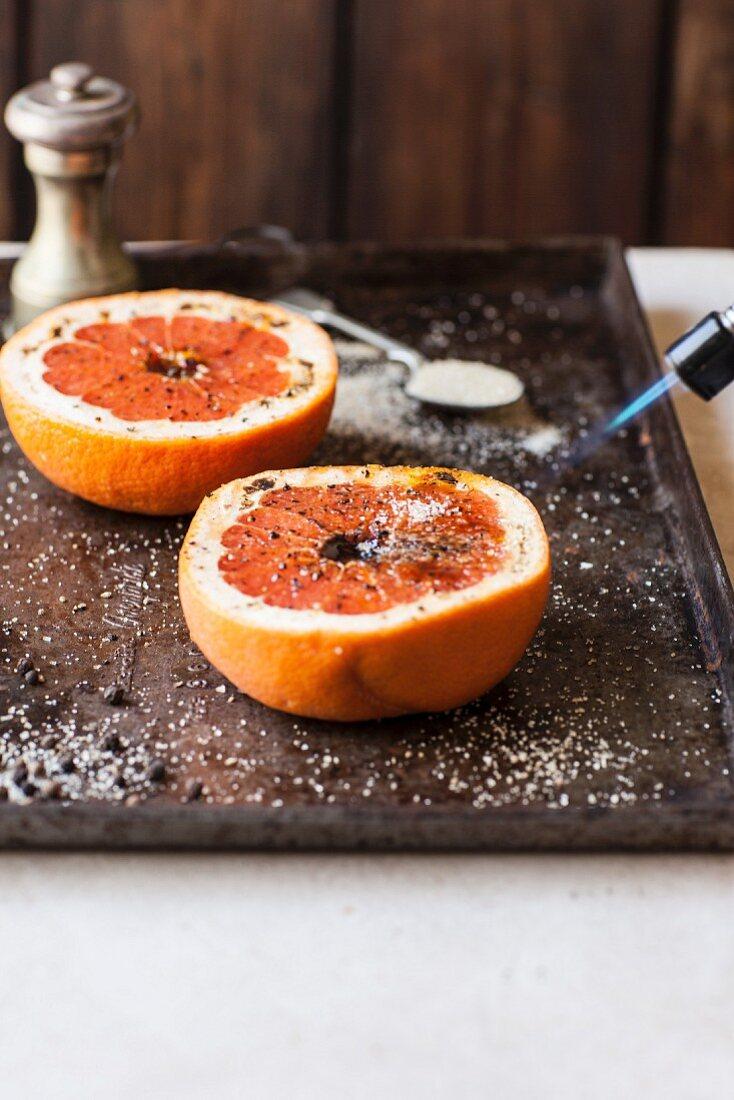 Baked grapefruit halves being caramelised
