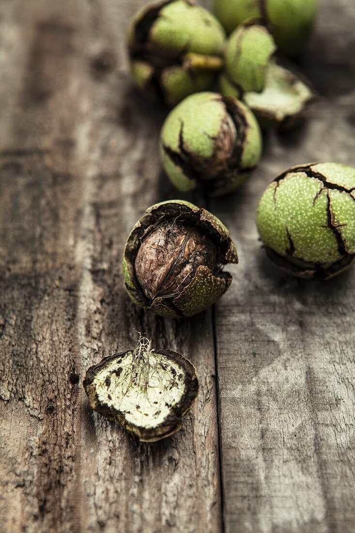 Fresh walnuts with green shells on a wooden surface