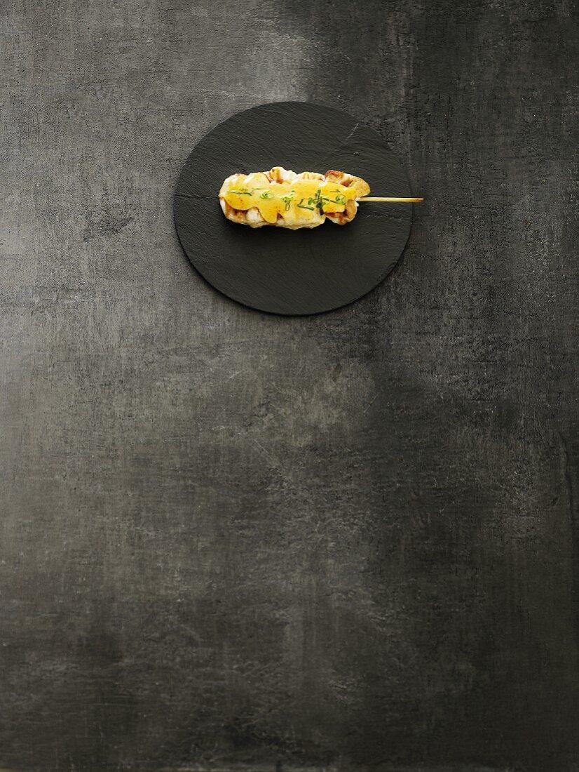 A kushi skewer on a round slate dish