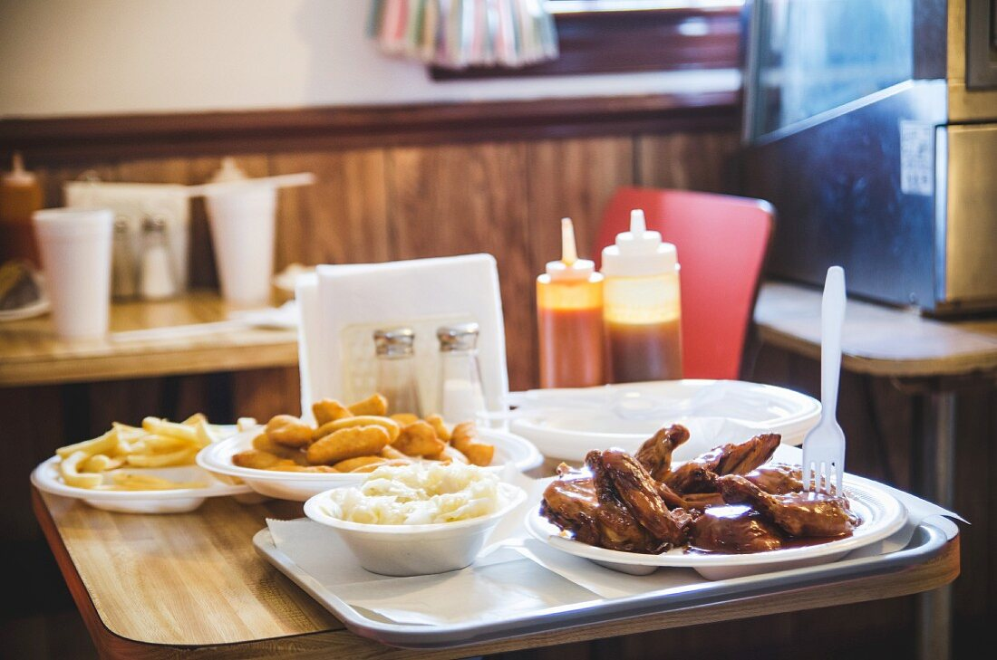 Chicken wings, coleslaw, hushpuppies and chips on a table in a restaurant