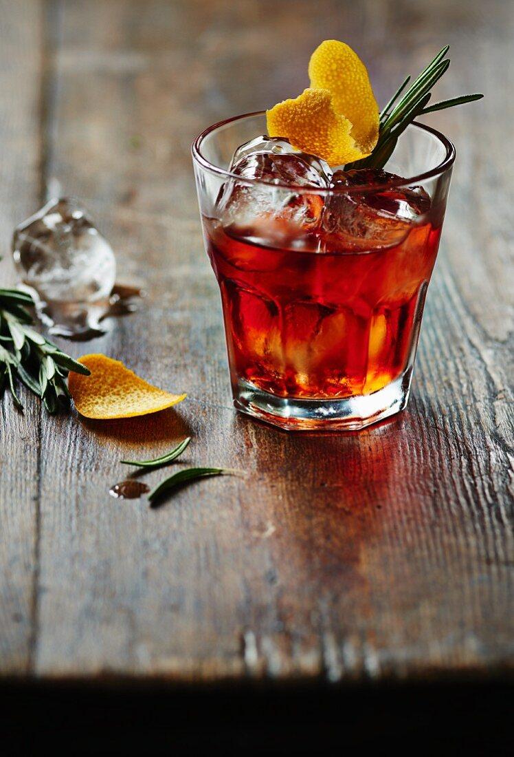 Negroni on ice with rosemary and lemon zest