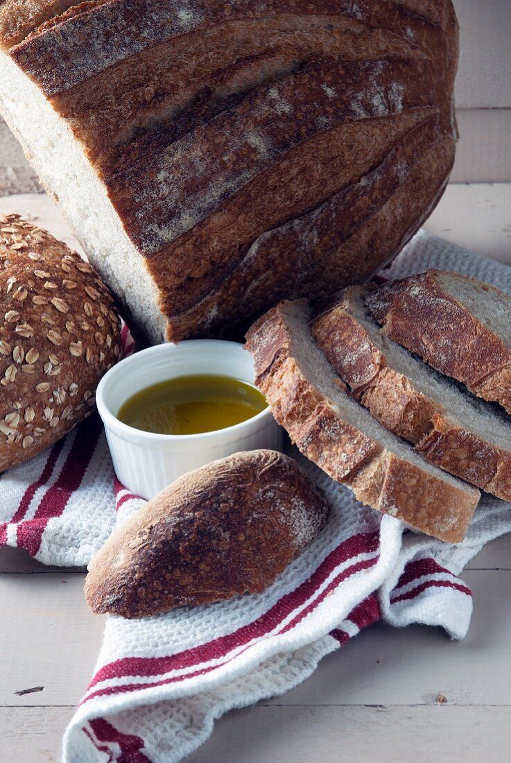 Various types of bread and a dish of olive oil