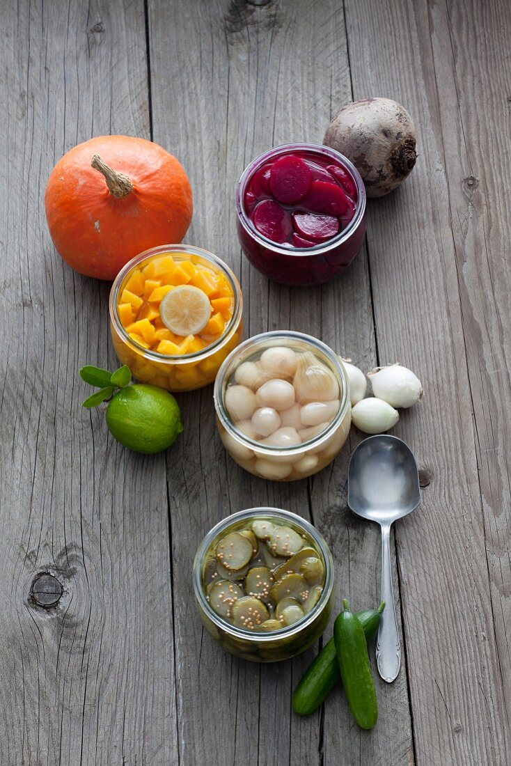 Various types of pickled vegetables in jars on a wooden surface