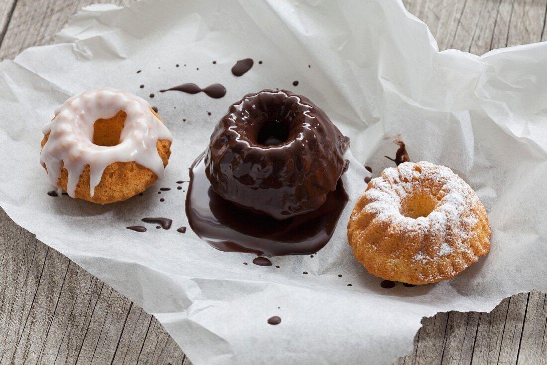 Three mini Bundt cakes with icing, chocolate glaze and icing sugar