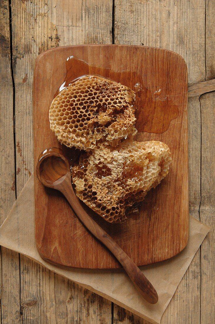 Honigwaben von Wildbienen auf Holzbrett mit Holzlöffel