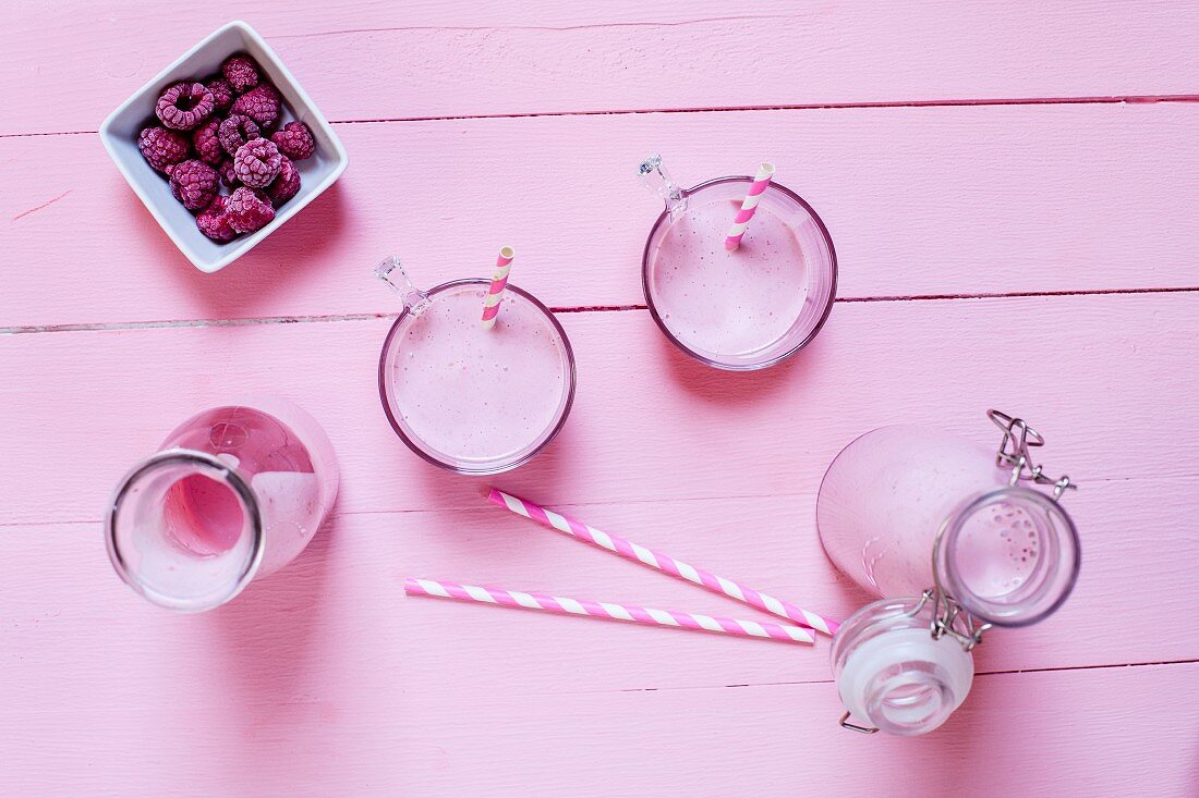 Raspberry smoothies on a pink wooden surface (seen from above)