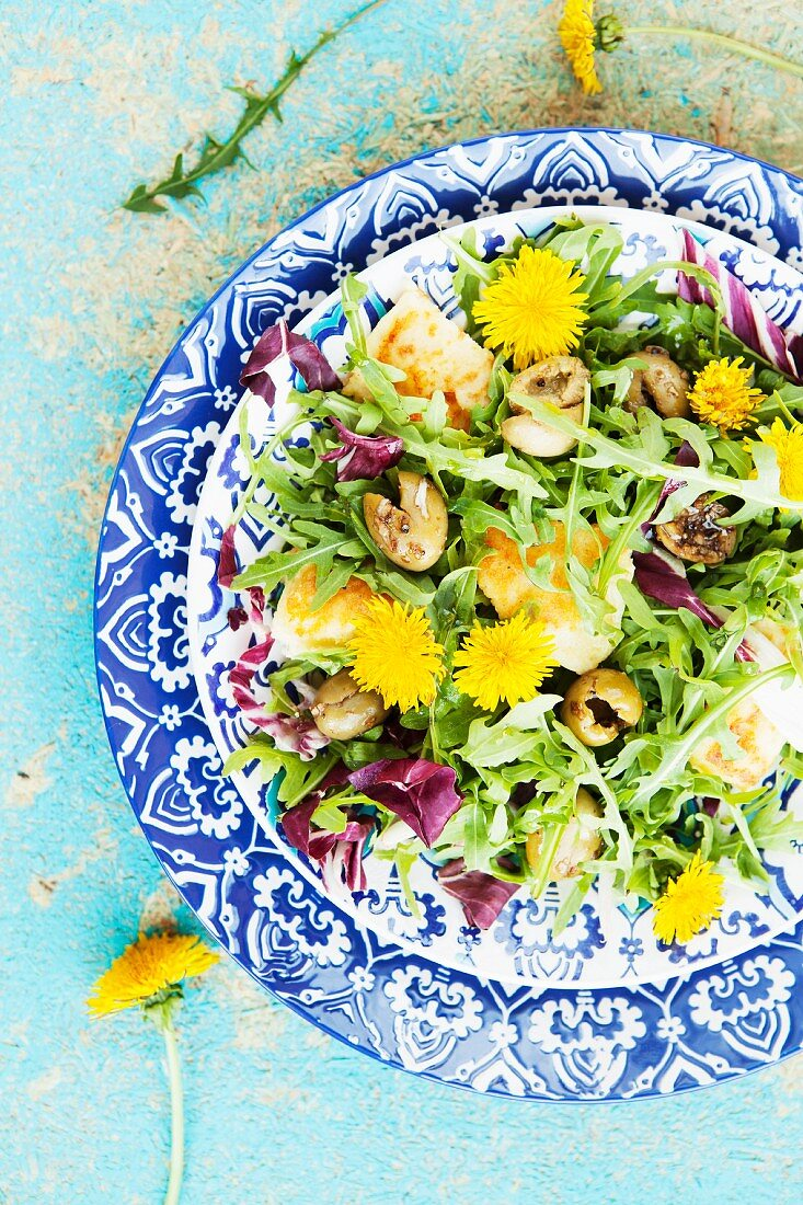 A mixed leaf salad with polenta, olives and dandelion flowers