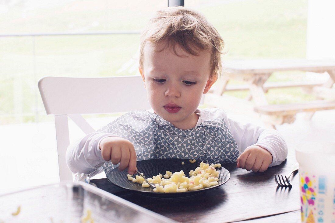 A little boy eating pasta