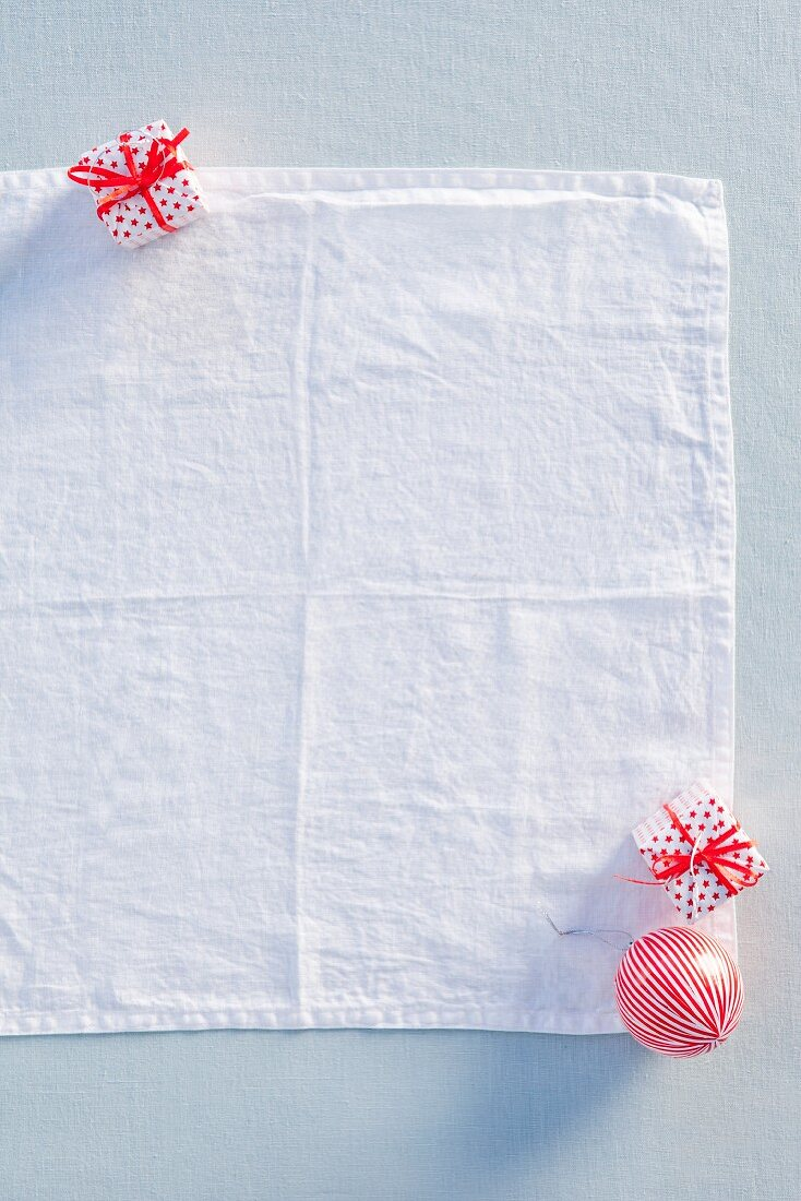 White linen napkin, tiny gift box and Christmas tree bauble