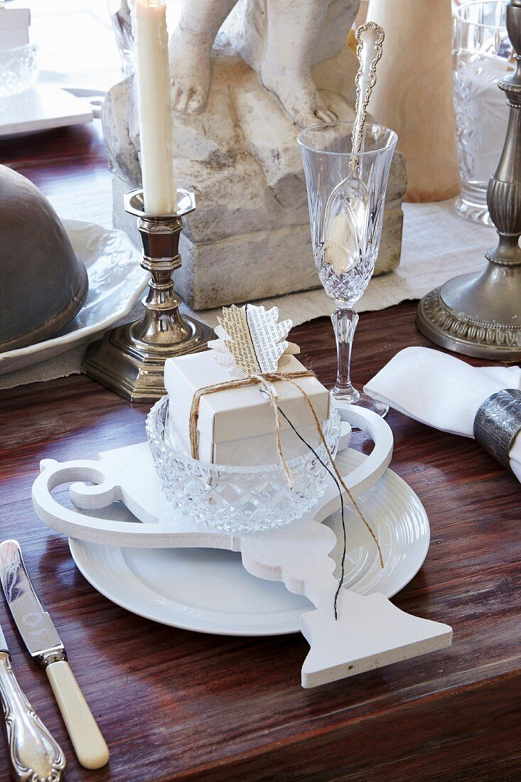 White place setting with vintage-style paper decoration, Champagne flute and silver candlestick on wooden table