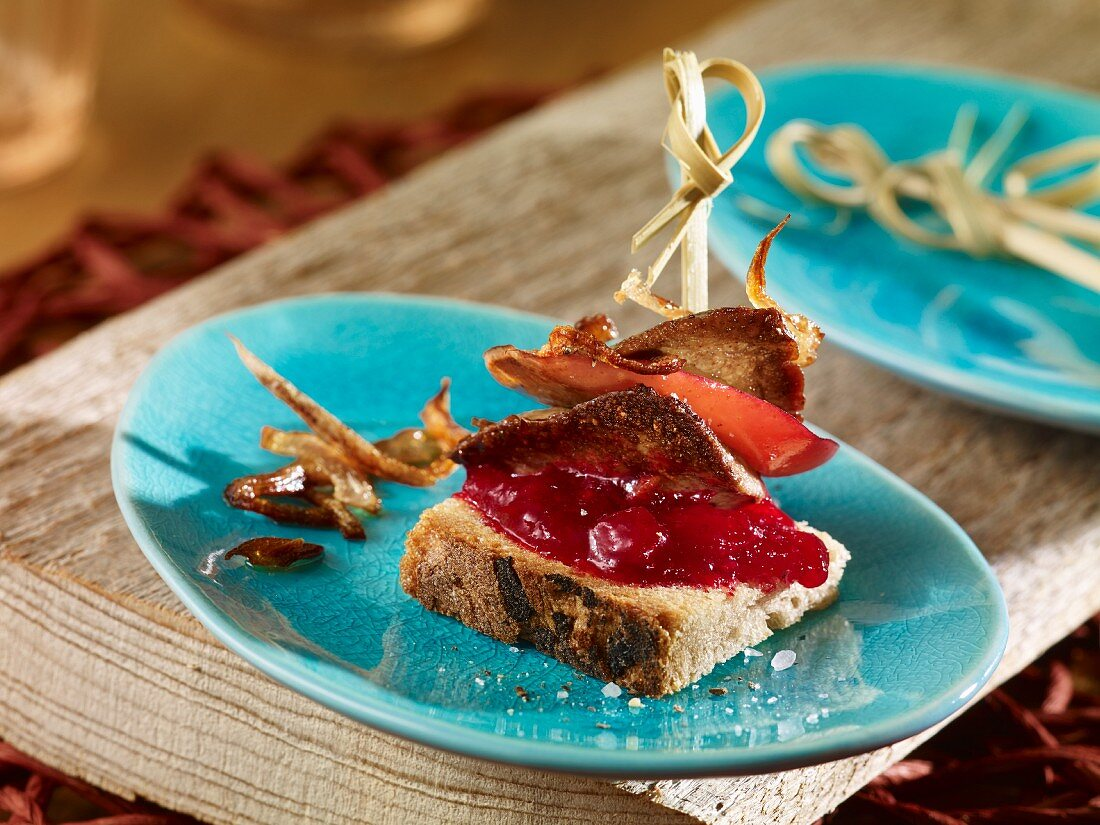Rabbit liver skewers with onion rings, apple slices and lingonberry compote on a slice of bread