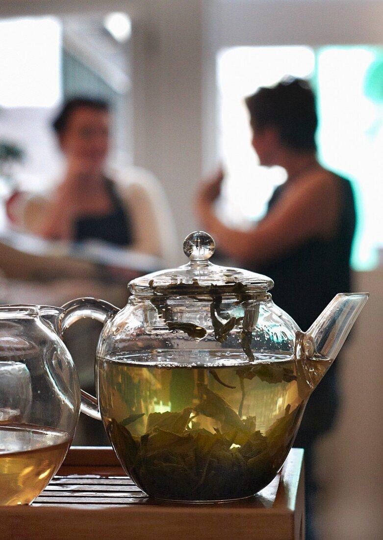 Green tea in a glass teapot in a restaurant