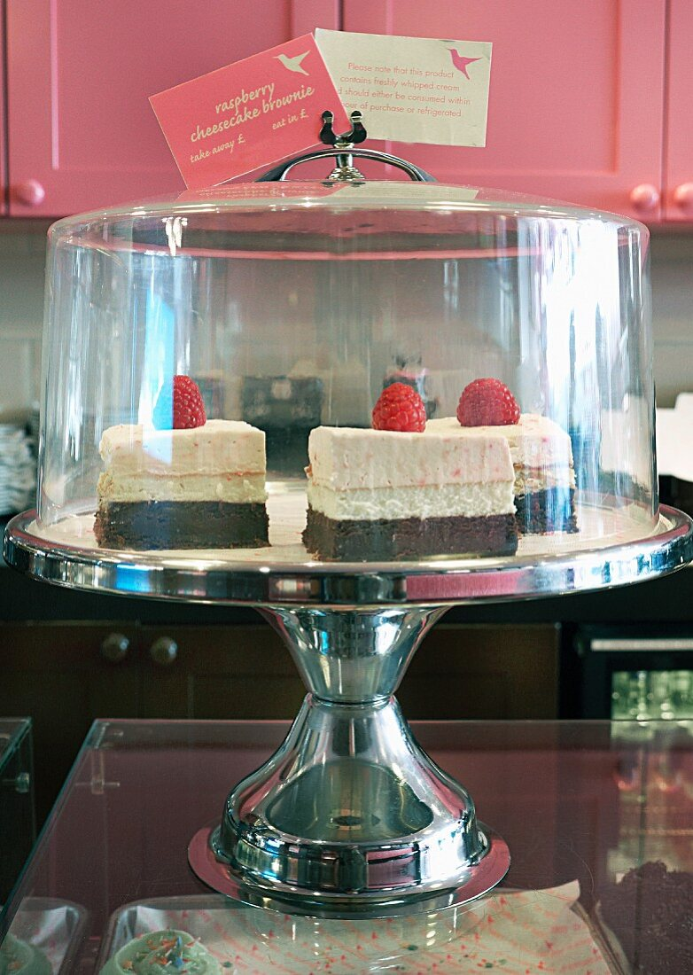 Raspberry cakes on a cake stand under a glass cloche for teatime in a restaurant