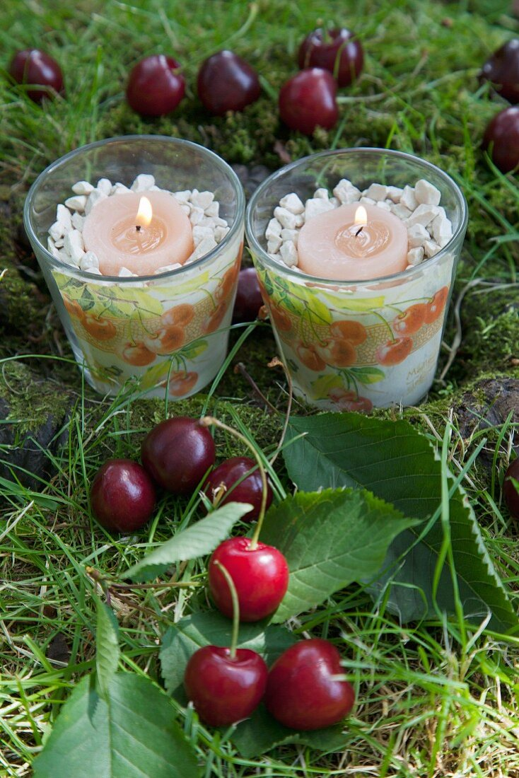 Tealight holders with patterns of cherries among cherries on grass