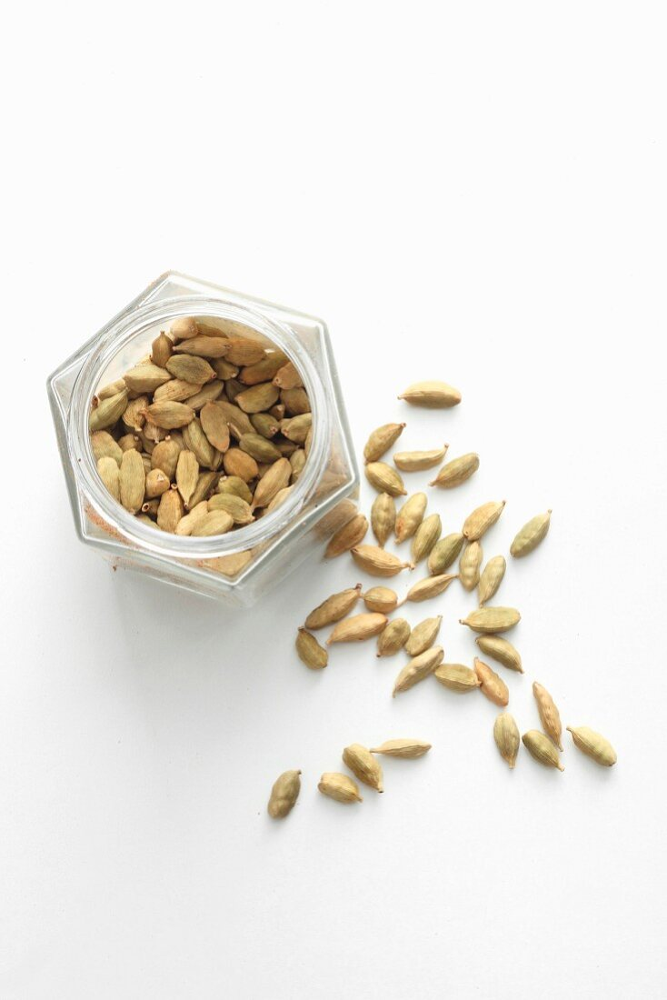 Cardamom pods in a jar and next to it