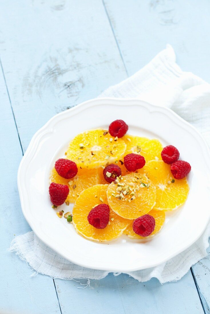 Orange slices topped with raspberries and chopped pistachio nuts