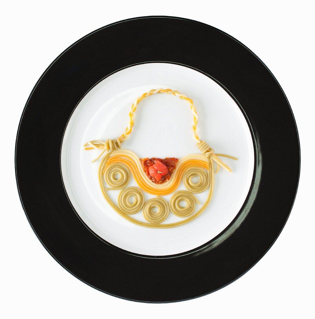 Fashion food: tri-coloured spaghetti with tomato sauce as a handbag