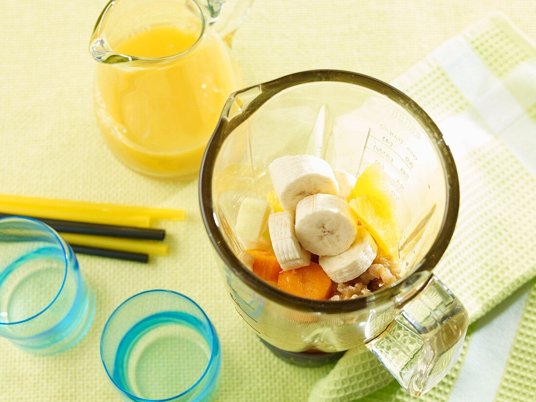 Ingredients for a banana and carrot smoothie in a blender