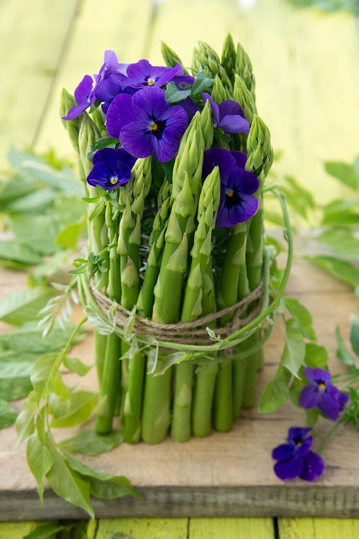 Table decoration made from green asparagus and tufted pansies
