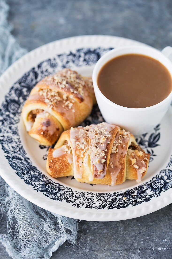 An almond croissant with white poppyseeds served with coffee