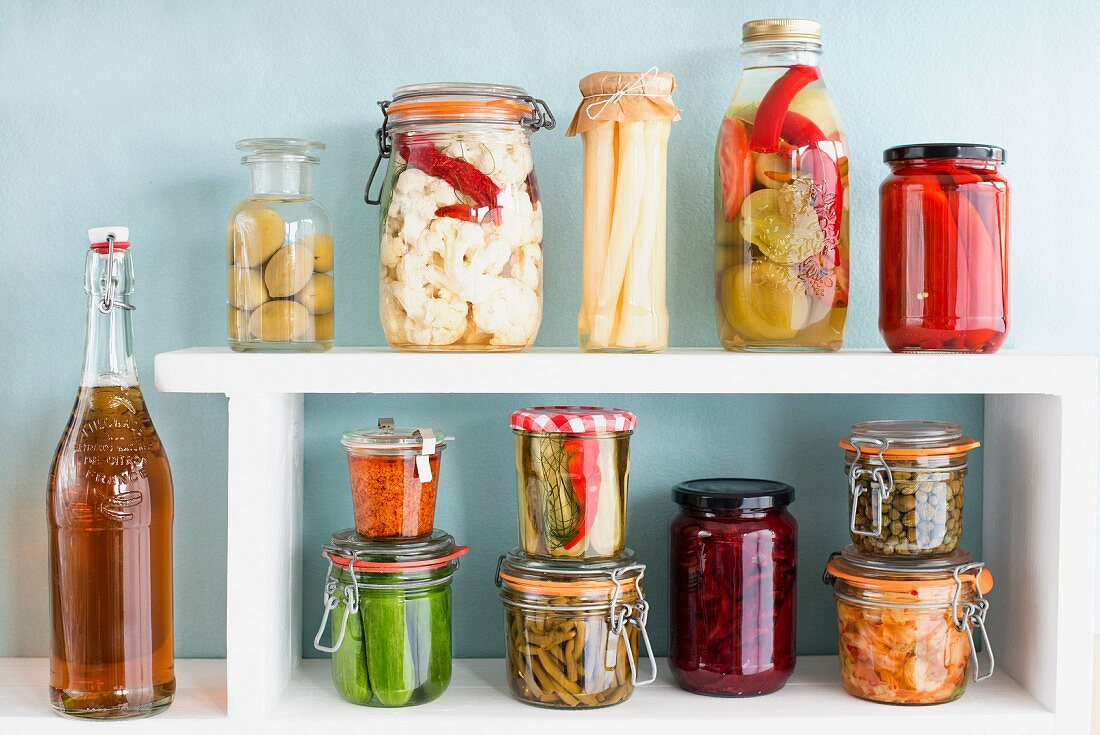 Various preserving jars with vegetables on a shelf with a bottle of home-brewed beer