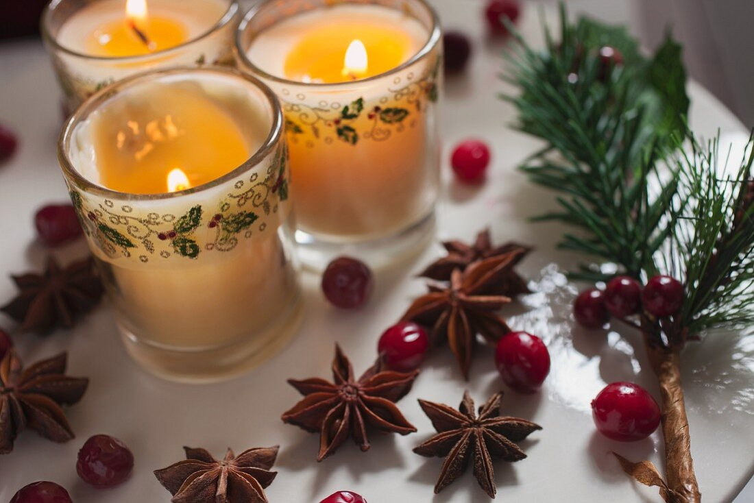 Three candles in glasses decorated for Christmas with bilberries and star anise