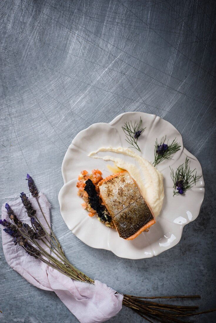 Fried salmon trout fillet on mashed potatoes with fennel, lavender and caviar