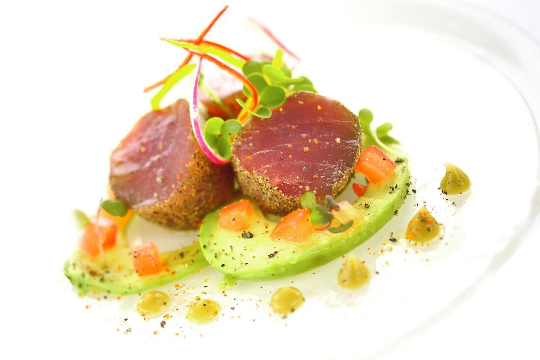 Tuna fish medallions with a crumb crust served with avocado, tomatoes and wasabi sauce