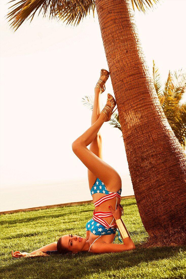 Junge Frau in Bikini macht Schulterstand an Palme