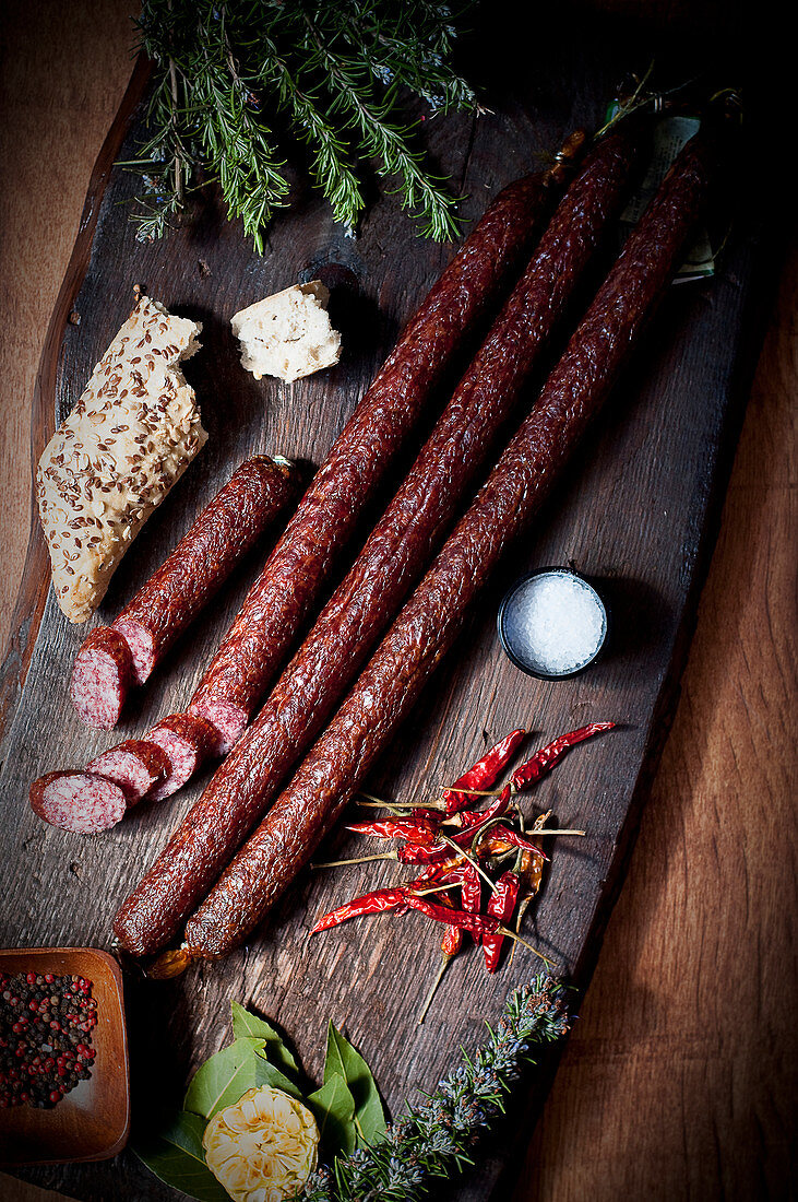 Long pork sausages with flaxseed rolls and dried chilli peppers on a wooden chopping board
