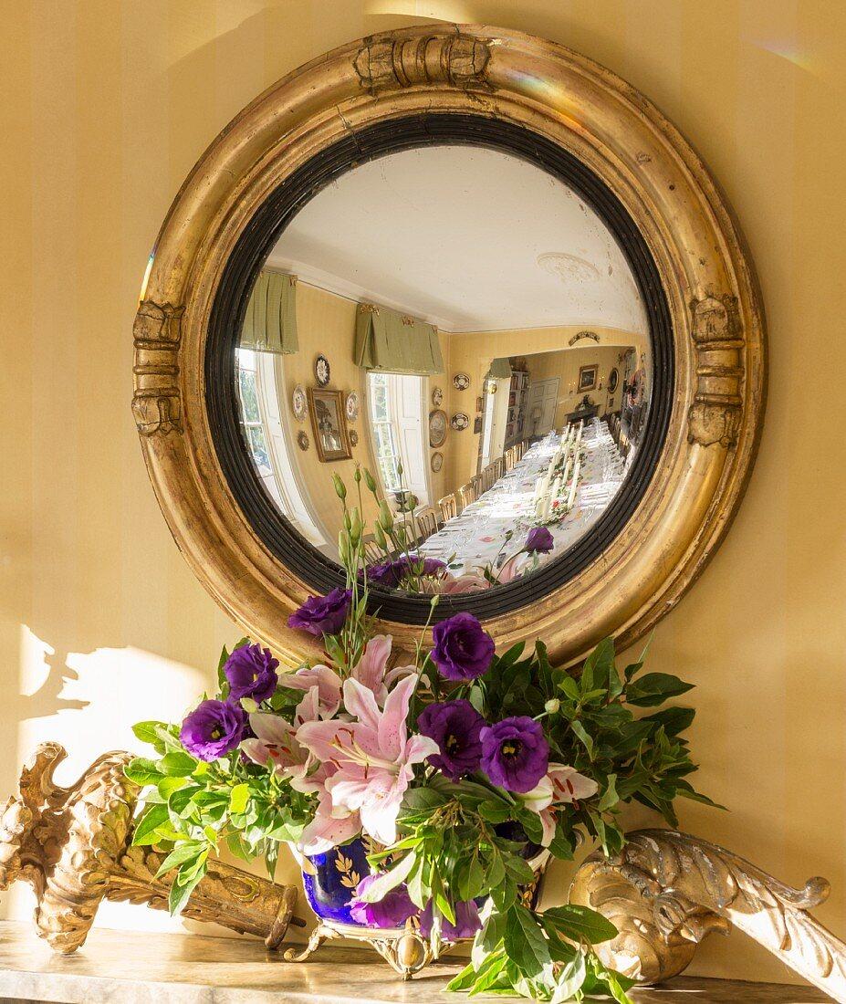 Festliche Tafel spiegelt sich in antikem Wandspiegel über dem Kamin im Salon eines Privathauses in Suffolk, England