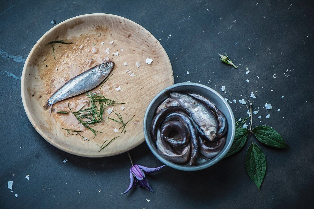 An anchovy on a wooden plate and anchovies in vinegar in a metal container (see from above)