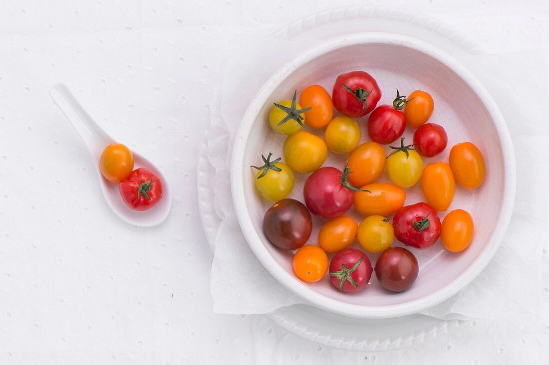 Various different coloured tomatoes in a porcelain bowl and on a spoon (seen from above)