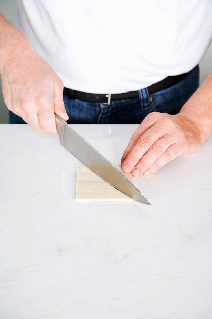 A wonton sheet being cut into triangles with a knife