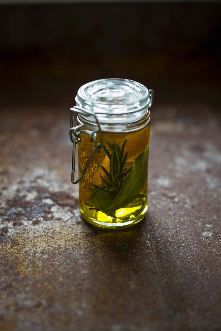 A jar of oil with orange zest and herbs