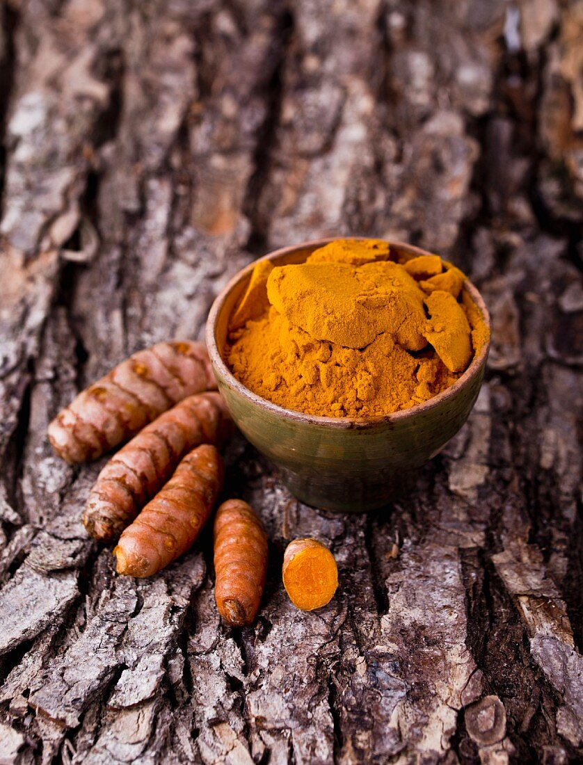 Turmeric, whole and ground, on a piece of bark