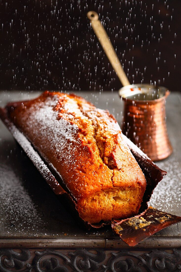 Arabian coffee cake being dusted with sugar