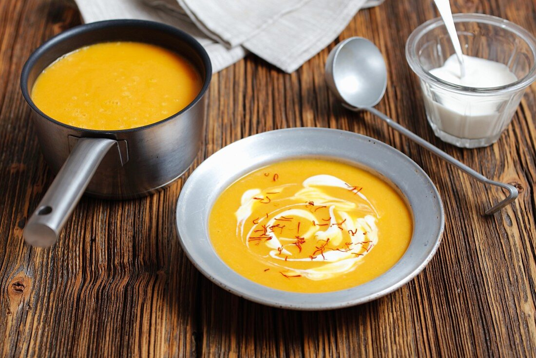 Cream of pumpkin soup garnished with cream and saffron